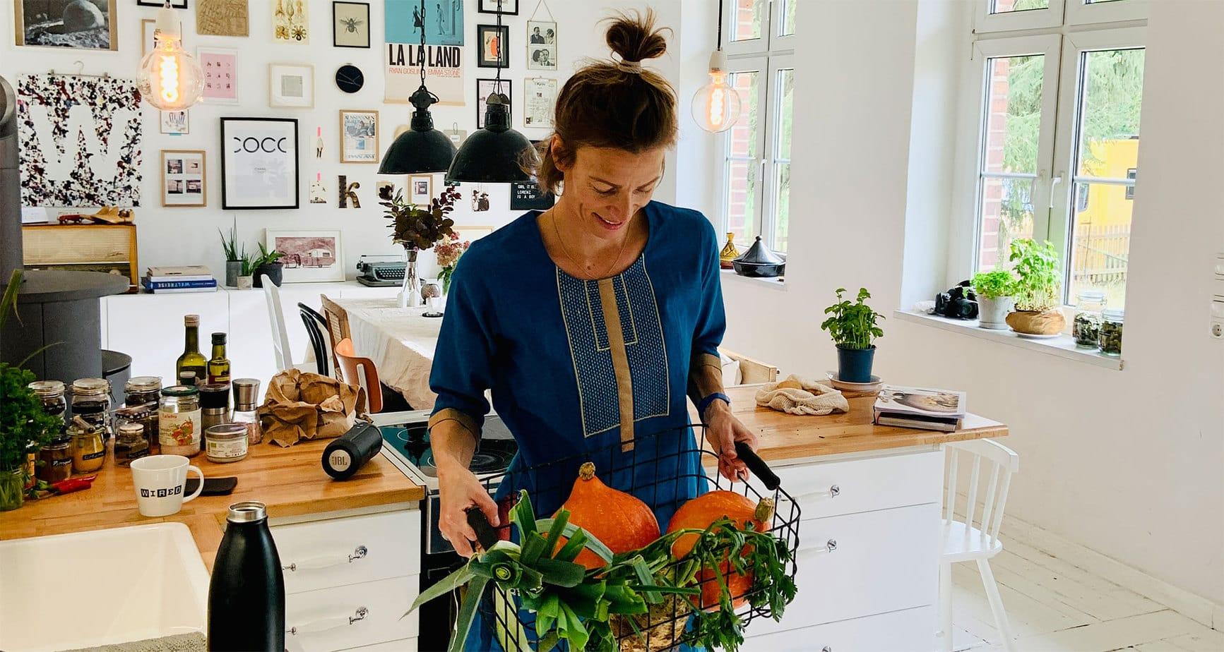Franzi von Nahrungsglück hält in der Küche einen Gemüsekorb mit Gemüse für ihre ayurvedischen Gerichte.
